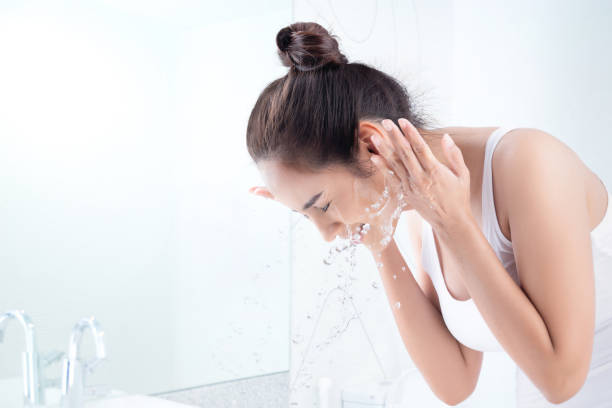 Beautiful woman washing face in the bathroom stock photo