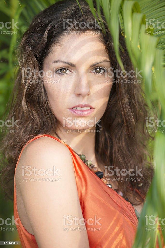 Beautiful woman watching the tropical sunset, palm garden royalty-free stock photo