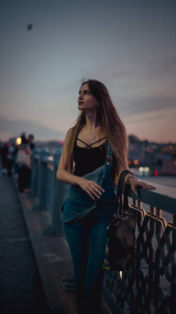 gün batımı pc'den bak haliç köprüsünde görünümünü izlemek güzel kadın - byakkaya stok fotoğraflar ve resimler