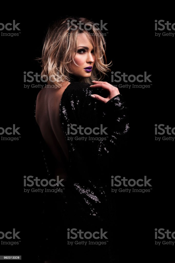 beautiful woman wearing a black shiny dress with open back stock photo
