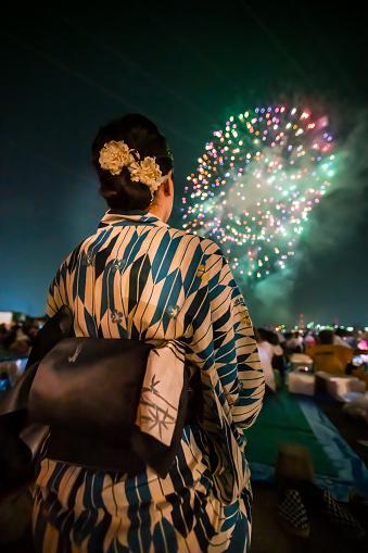Beautiful woman wearing a kimono looking up at fireworks