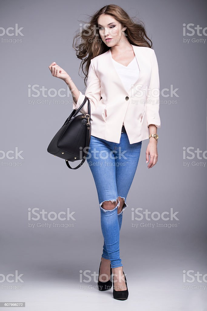 Beautiful woman wearing a pink jacket and holding black bags stock photo