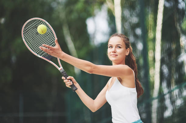 Eine schöne Frau, die einen Sportbekleidungs-Tennisball trägt. – Foto