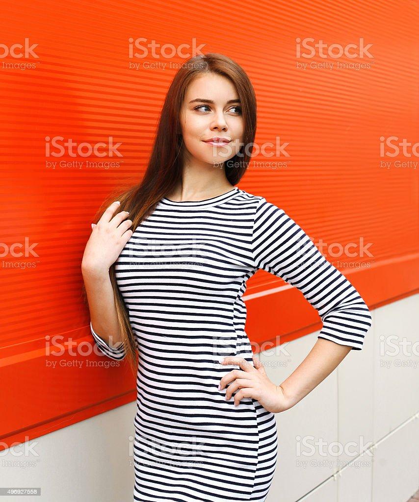 89e683f6d1c6 Bella donna che indossa un abito a righe in città in rosso foto stock  royalty-