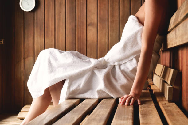 A beautiful woman wearing a white towel takes a sauna: The sauna is made of wood with a large window with a view of the snow. A beautiful woman wearing a white towel takes a sauna: The sauna is made of wood with a large window with a view of the snow. Concept of: relax, vacation, wellness center. sauna stock pictures, royalty-free photos & images