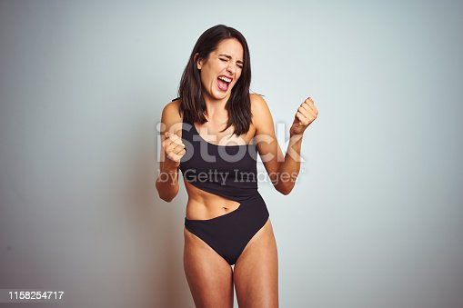 Beautiful woman wearing bikini swimwear over white isolated background very happy and excited doing winner gesture with arms raised, smiling and screaming for success. Celebration concept.