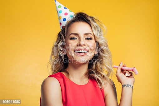 istock Beautiful woman wearing birthday cap 908041580