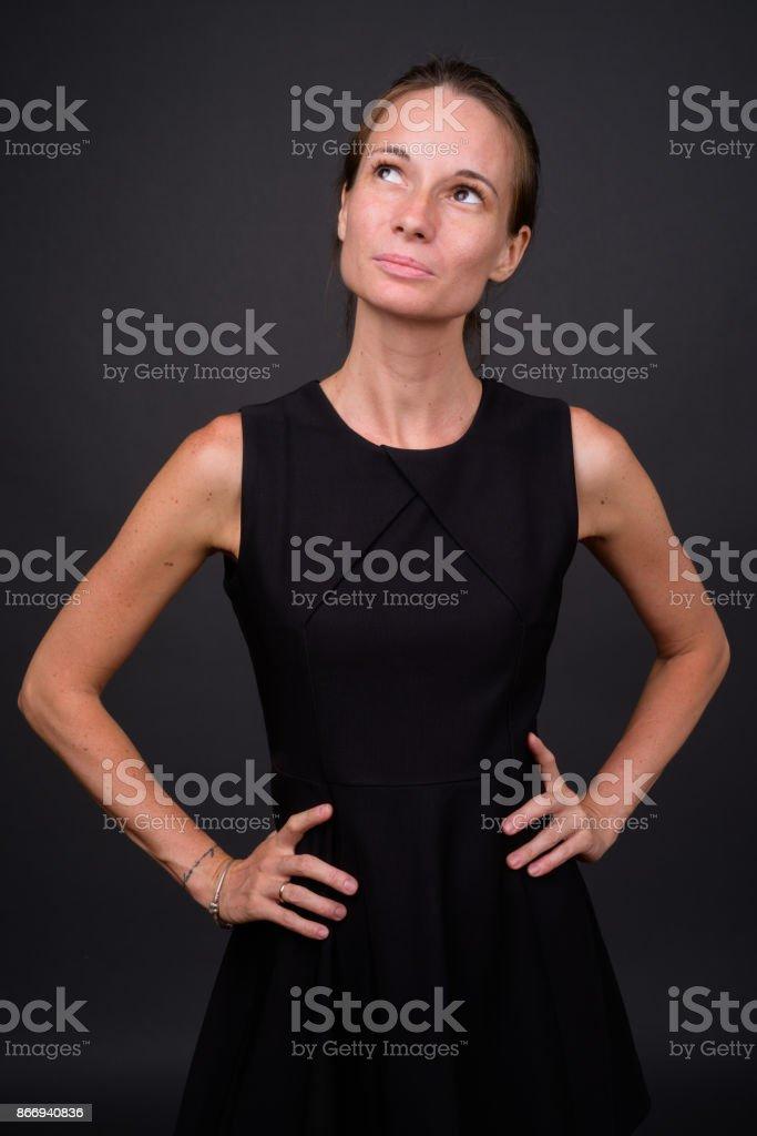 8f673da51f3 Beautiful woman wearing black sleeveless dress against gray background  royalty-free stock photo