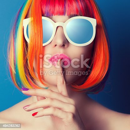 istock beautiful woman wearing colorful wig and white sunglasses agains 494283262
