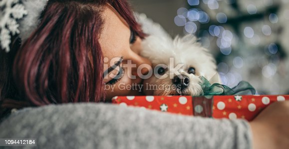 Beautiful woman wearing dear ear playing with cute dog