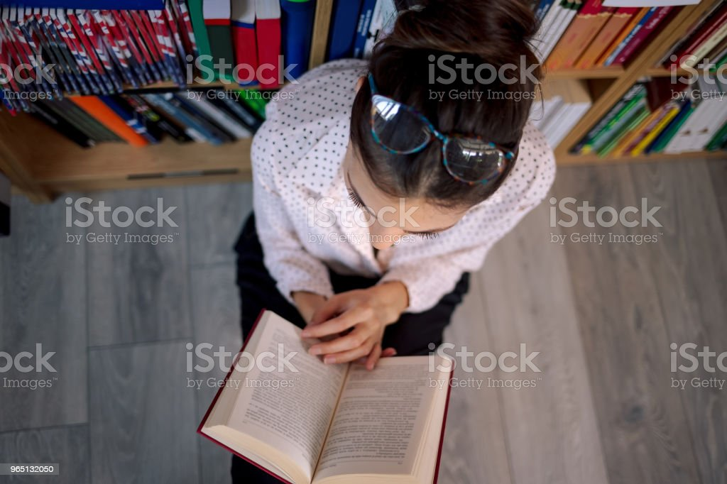 Beautiful woman wearing glasses reading a book in the book shop. zbiór zdjęć royalty-free