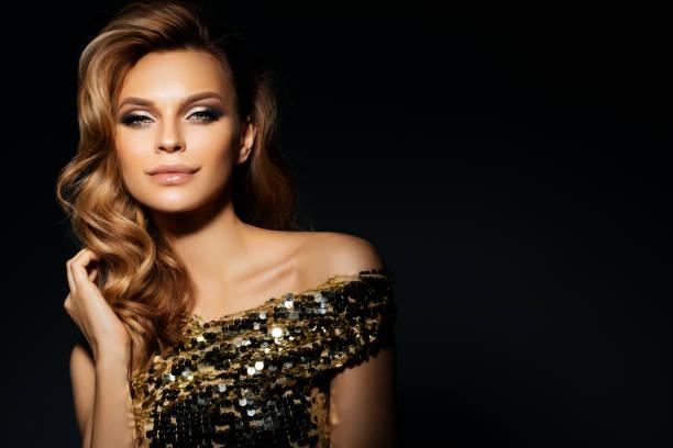 schöne frau mit goldenen kleid - lange abendkleider stock-fotos und bilder