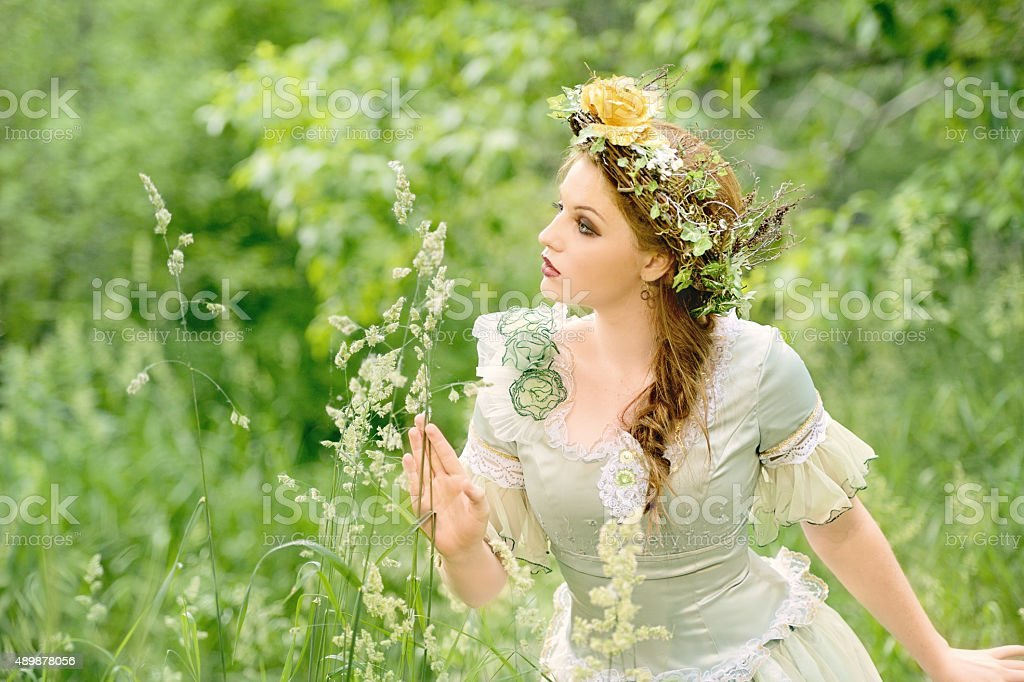 Beautiful Woman Wearing Leafy Laurel and Retro Dress In Nature stock photo