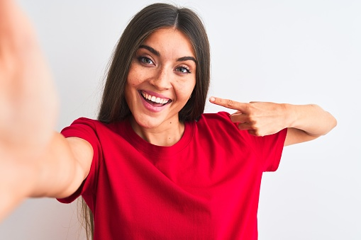 Beautiful woman wearing red t-shirt make selfie by camera over isolated white background very happy pointing with hand and finger