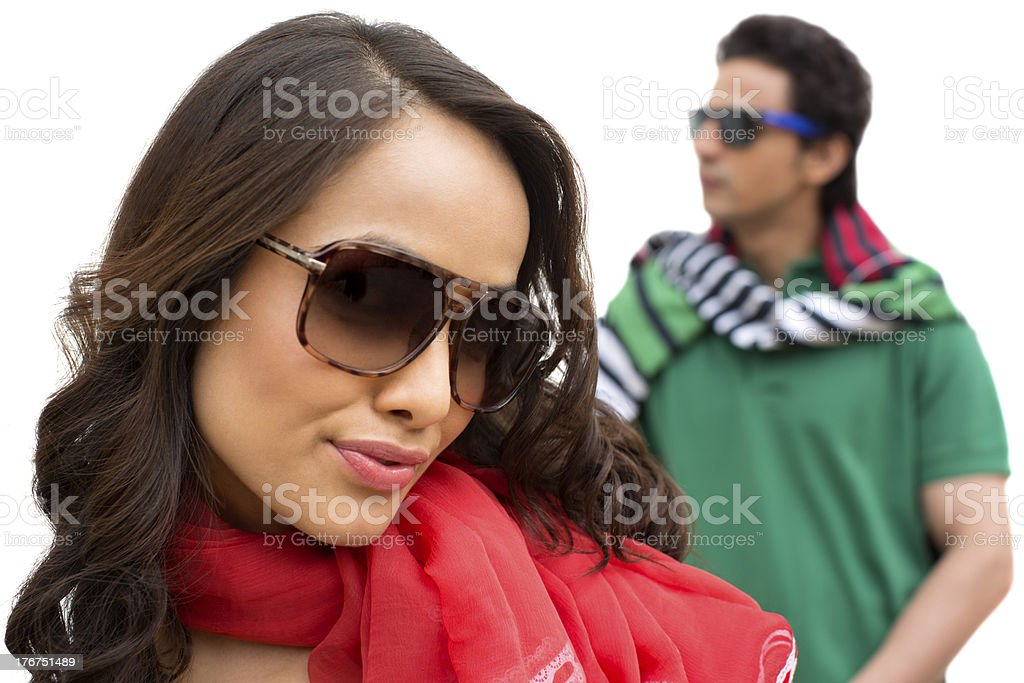Beautiful woman wearing sunglasses with her boyfriend in background royalty-free stock photo