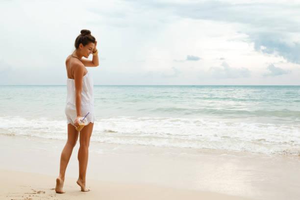 Beautiful woman wearing white jumpsuit walk on the beach stock photo