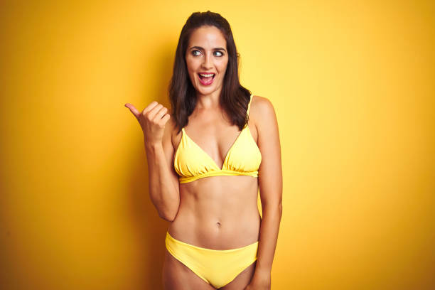 28cef849598 Beautiful woman wearing yellow bikini on summer over isolated yellow  background smiling with happy face looking