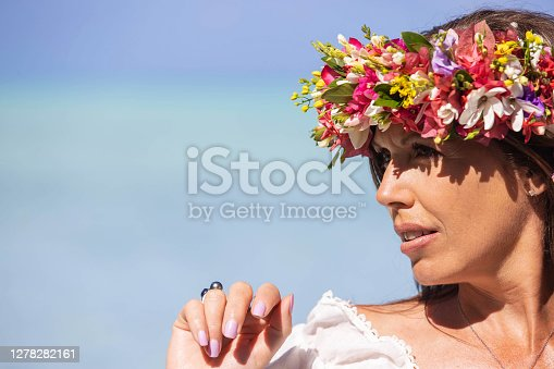 Pretty woman wears colorful flower crown while on tropical island vacation in Bora Bora, French Polynesia