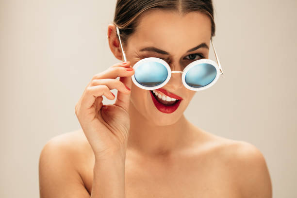 Beautiful woman winking with glasses Portrait of beautiful young woman with sunglasses. Female fashion model winking with glasses against beige background. mischief stock pictures, royalty-free photos & images