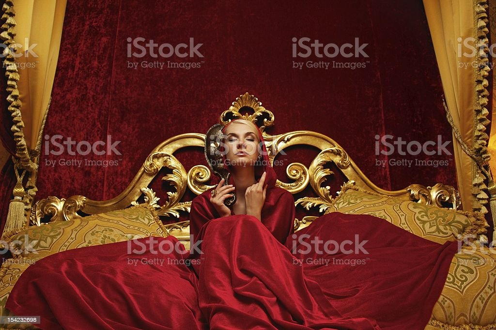Beautiful woman with a carnival mask sitting in bed royalty-free stock photo