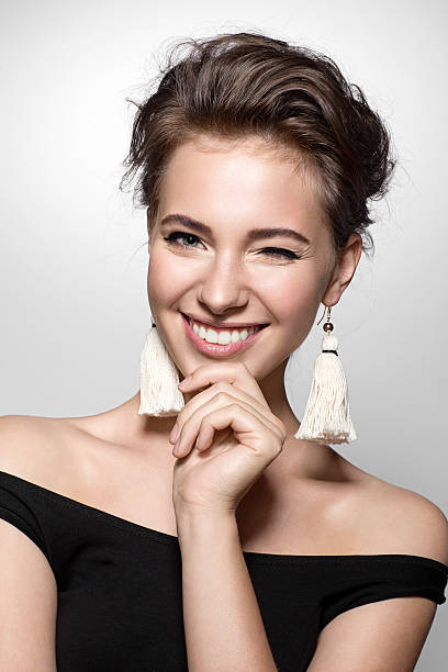 beautiful woman with a charming smile in a black dress - lustige augenbrauen stock-fotos und bilder