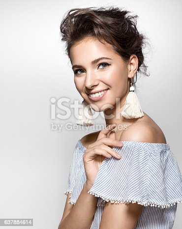 Beautiful woman with a charming smile in a summer dress and earrings tassels