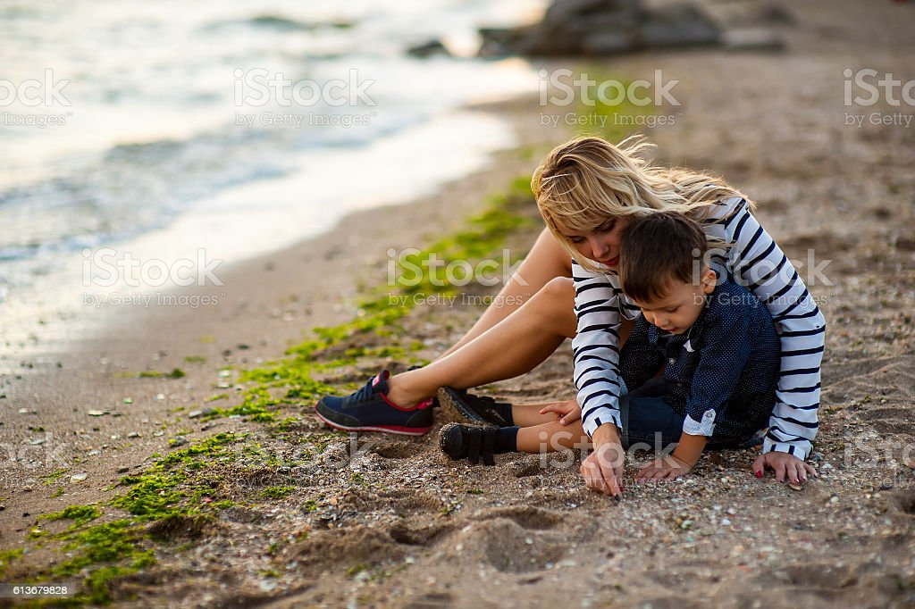 Beautiful woman with a child on the beach stock photo
