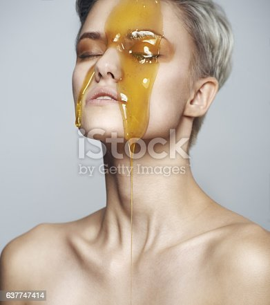 istock Beautiful woman with a honey on her face 637747414