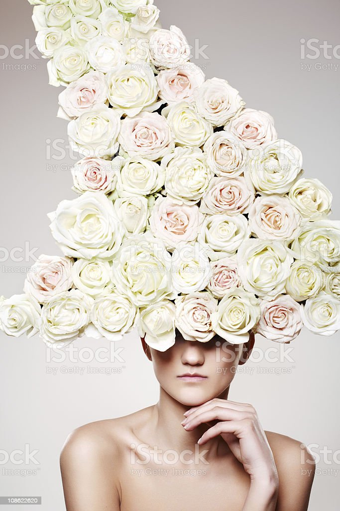 Beautiful woman with a rose headwear stock photo