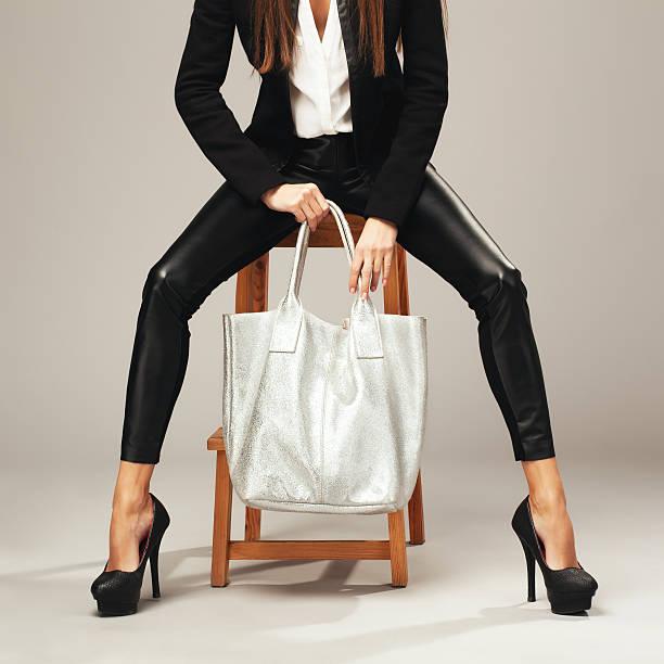 schöne frau mit einem silber mode tasche - leder leggings stock-fotos und bilder