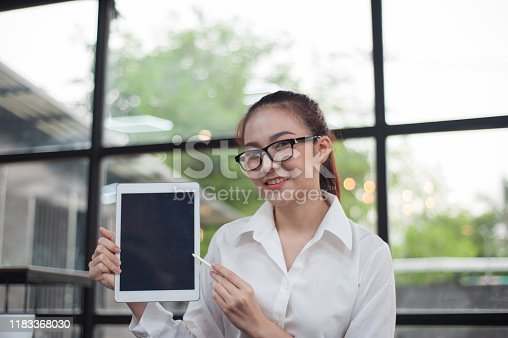 863476202 istock photo A beautiful woman with a smiling face looking and holding a tablet while working in the office. 1183368030