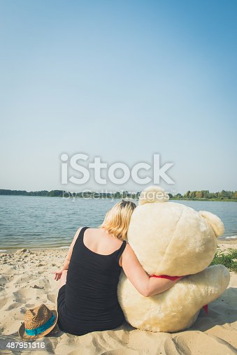 505935220istockphoto Beautiful woman with a teddy bear 487951316