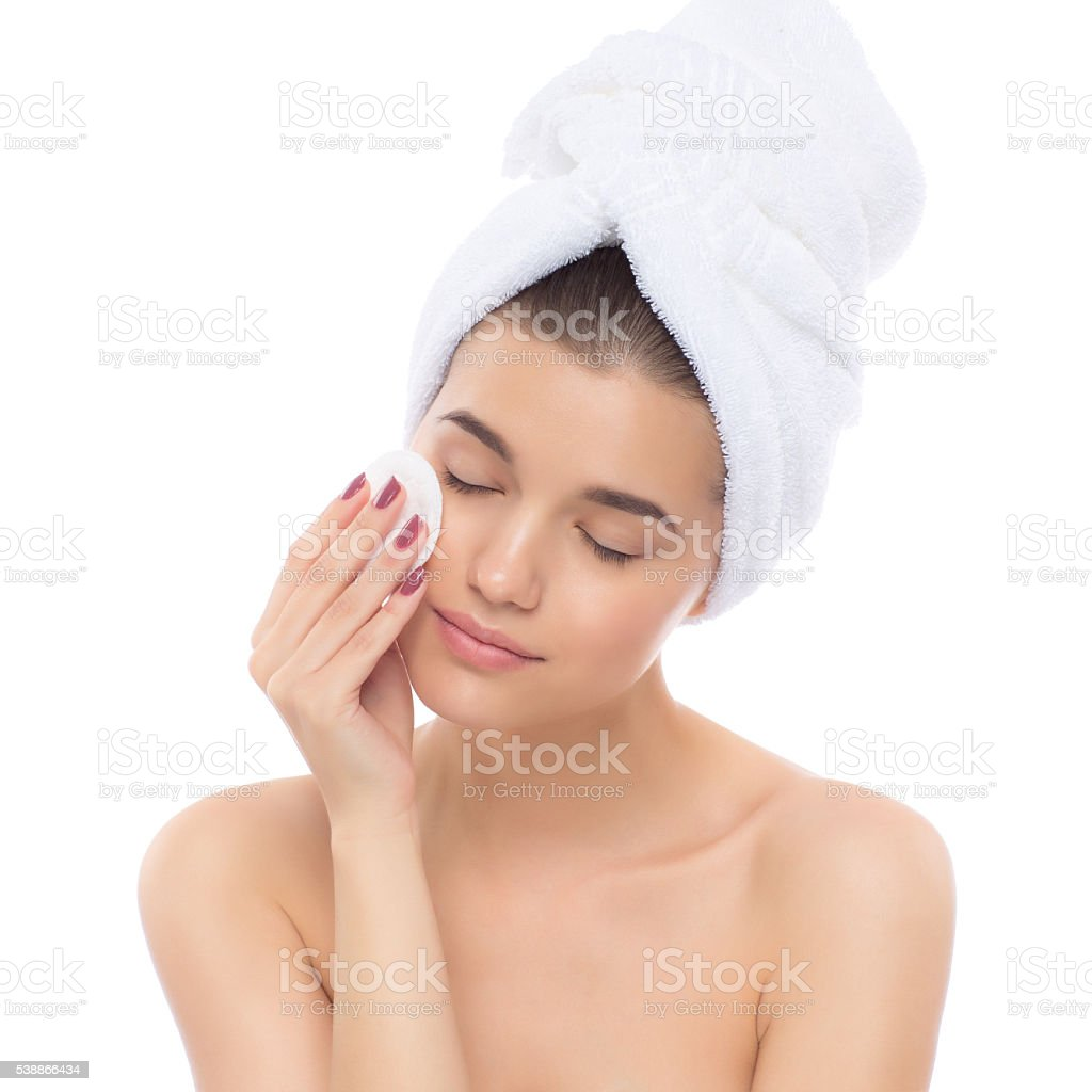 Beautiful woman with a towel on his head. Removing makeup. stock photo