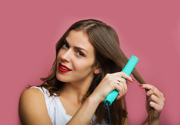 beautiful woman with a wavy hair holding a hair iron - ironing stock photos and pictures