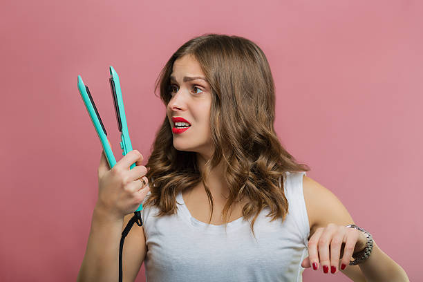 Beautiful woman with a wavy hair holding a hair iron stock photo