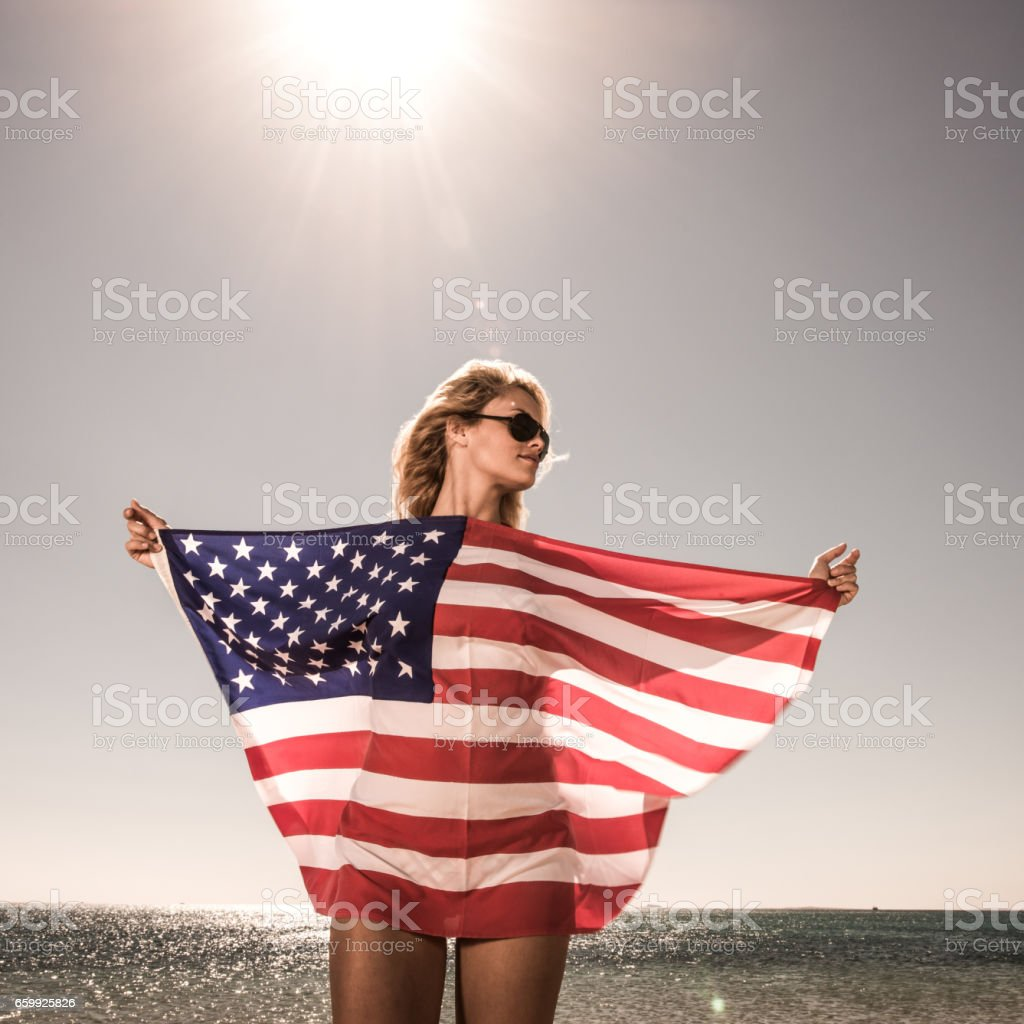 Beautiful woman with American flag in summer day. stock photo