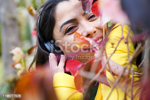 969233490 istock photo beautiful woman with autumn leaves and green eyes listening to music 1199777528