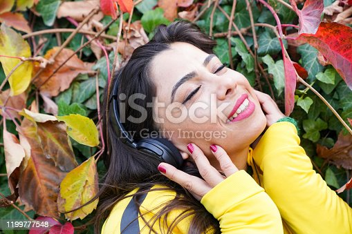 969233490 istock photo beautiful woman with autumn leaves and green eyes listening to music 1199777548
