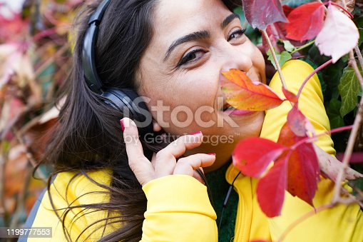 969233490 istock photo beautiful woman with autumn leaves and green eyes listening to music 1199777553