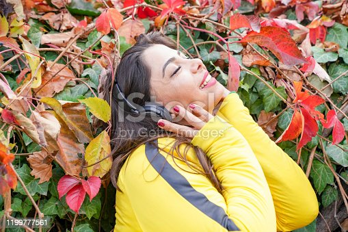 969233490 istock photo beautiful woman with autumn leaves and green eyes listening to music 1199777561