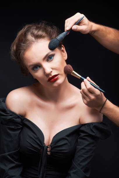 beautiful woman with beautiful brown hair in a dark dress on a dark background and the stylist does makeup stock photo
