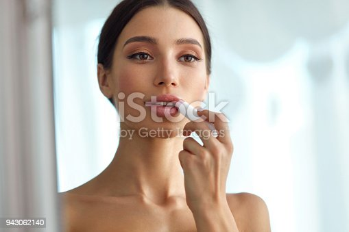 istock Beautiful Woman With Beauty Face Applies Balm On Lips. Skin Care 943062140