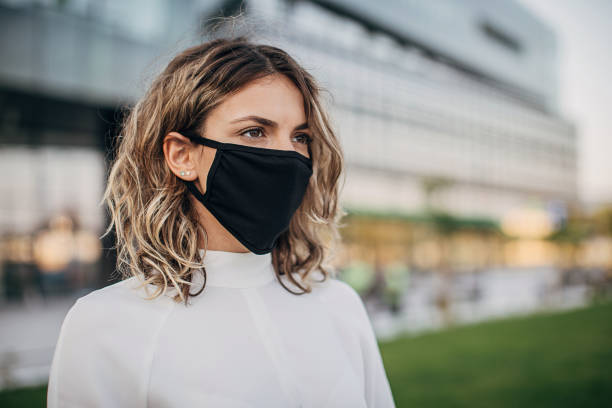 Beautiful woman with black face mask on the street stock photo