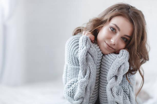 hermosa mujer con pelo rubio en un jersey de punto gris en una habitación brillante sobre un fondo gris - moda de invierno fotografías e imágenes de stock