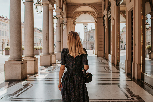 A beautiful woman with blond hair walks through the streets of the city. Girl enjoy holidays in Europe. Beautiful historical architecture. Italian weekend. Travel to Turin, Italy. Adventure lifestyle