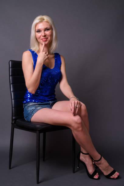 schöne frau mit blonden haaren tragen blaue pailletten ärmelloses top vor grauem hintergrund - pailletten shirt stock-fotos und bilder