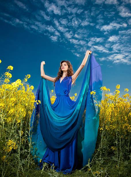 Schöne Frau mit blauen Kleid posieren in canola field – Foto