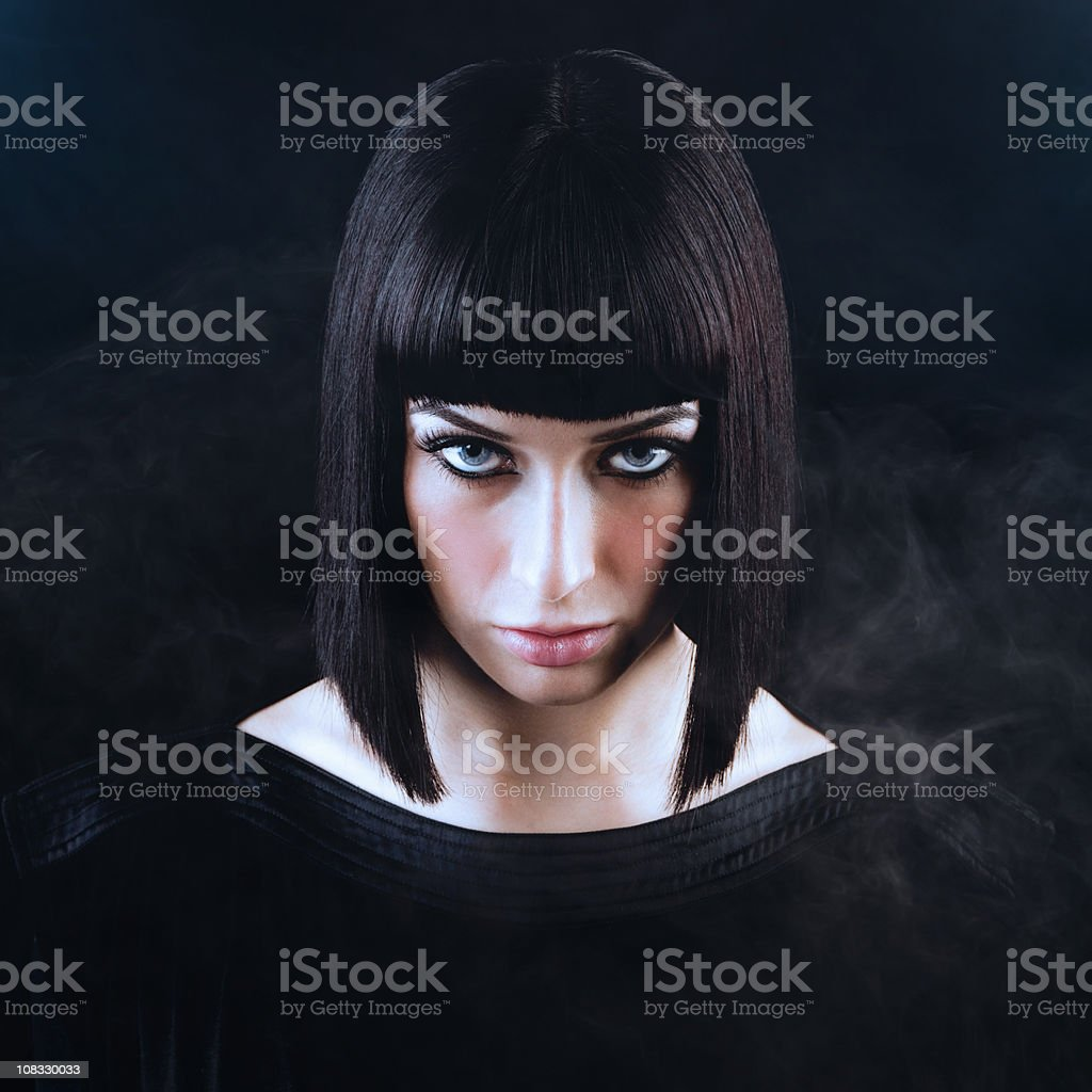 Beautiful Woman with Blunt Dark Hair and Smoky Black Background stock photo