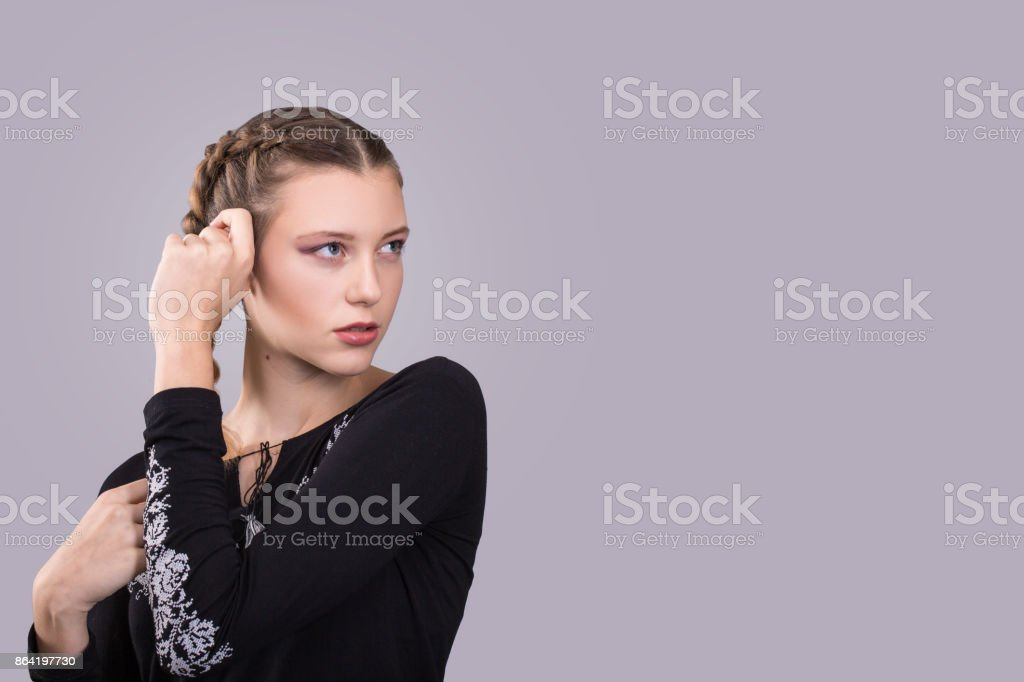 Beautiful woman with braids. Expressive girl on gray background royalty-free stock photo