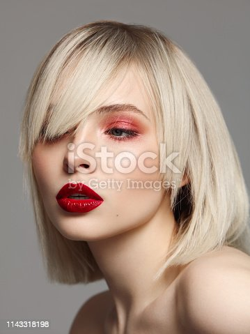 Studio portrait of beautiful woman with bright professional make-up and bob haircut